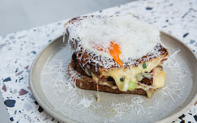 A cheese toastie topped with an egg