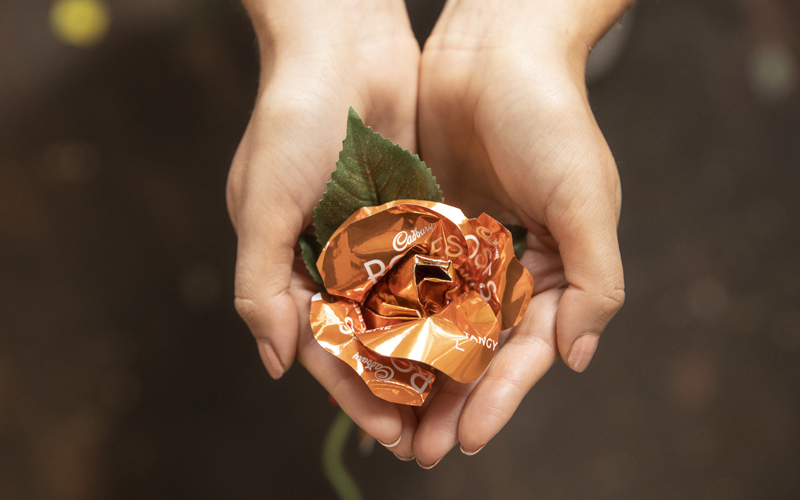 Womans holding Cadbury's Roses flowers in her hands